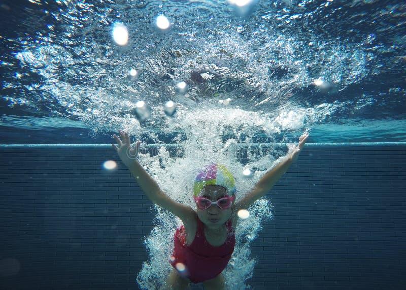 Glückliches asiatisches Kind, das unter Wasser im Sommer schwimmt stockbild
