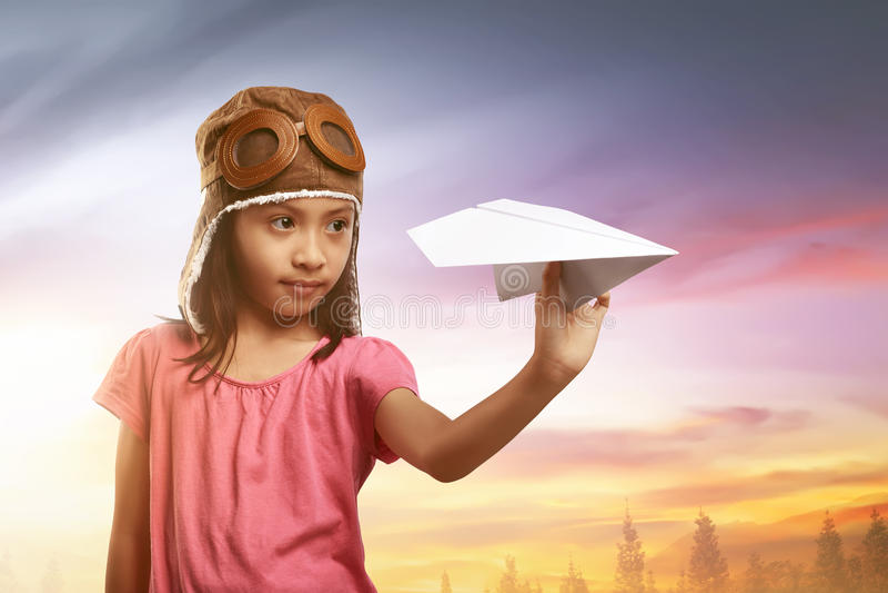 Glückliches asiatisches Kind im Fliegersturzhelm, der mit Papierflächen spielt lizenzfreies stockfoto