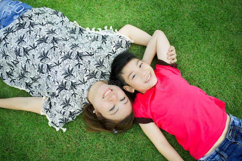 Glückliches asiatisches Kind mit Mutterspiel draußen im Park stockbilder