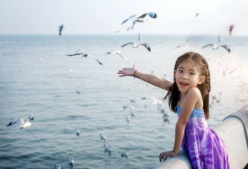 Glückliches asiatisches Kind wie Wind und Vogel auf Meerblick lizenzfreie stockfotografie