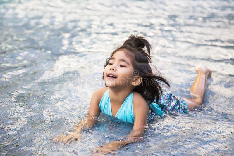 Glückliches asiatisches Mädchen auf Pool lizenzfreies stockfoto