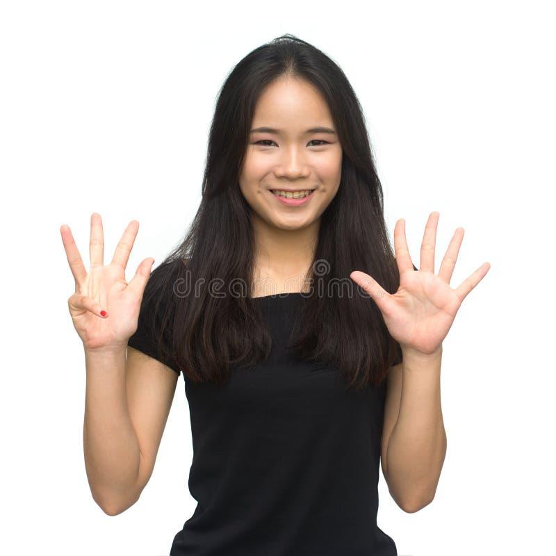 Glückliches asiatisches Mädchen, das bis neun zählt stockfotografie