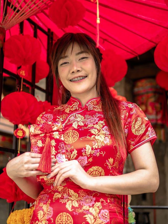 Glückliches asiatisches Mädchen, das roten Umschlag hält, um im Festival des Chinesischen Neujahrsfests zu geben Chinesisches neu stockbild