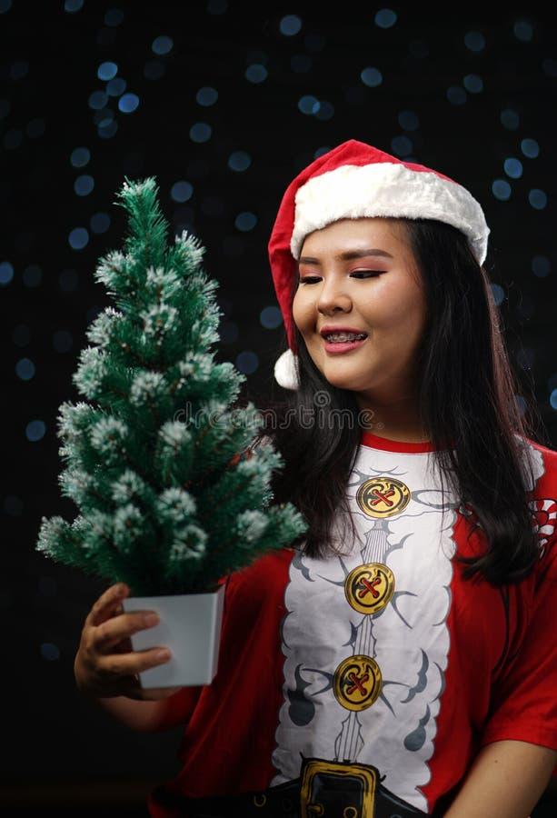 Glückliches asiatisches Mädchen, das Santa Costume Holding Small Christmas T trägt stockfotos