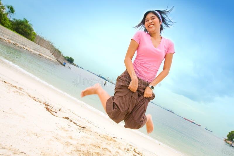 Glückliches asiatisches weibliches Tanzen auf Strand stockbilder
