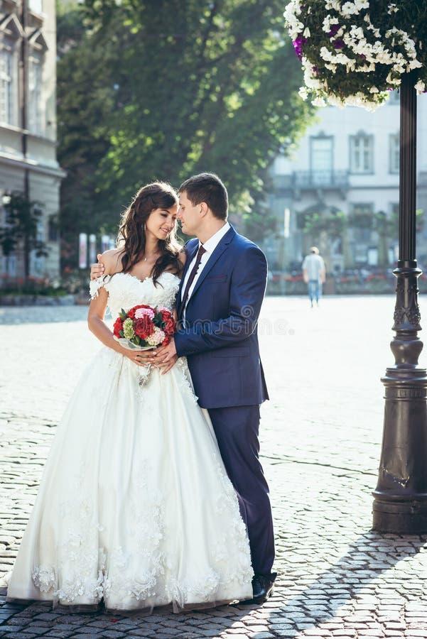 Glückliches attraktives Jungvermähltenpaar ist weich, berührend umarmend und Nasen in der sonnigen Straße In voller Länge Portrai lizenzfreie stockfotos