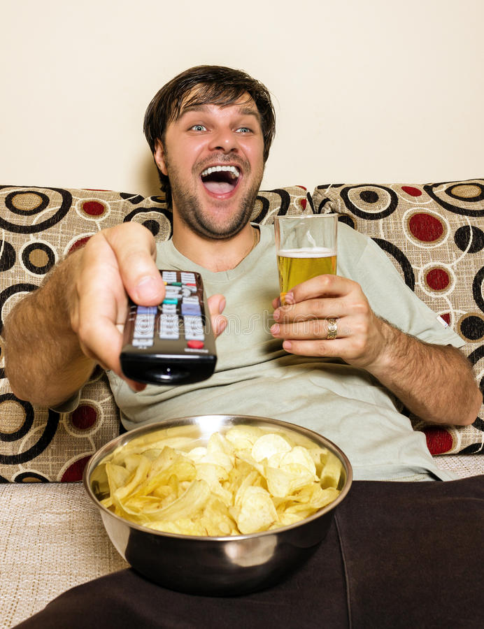 Glückliches aufpassendes Fernsehen des jungen Mannes, Kartoffelchips und dri essend stockfotografie