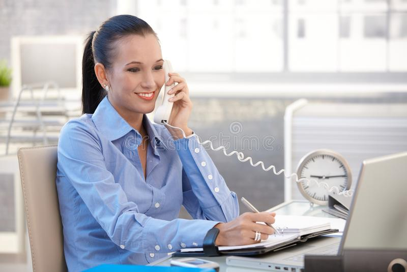 Glückliches Büroangestelltmädchen beim Telefonaufruf lizenzfreies stockfoto