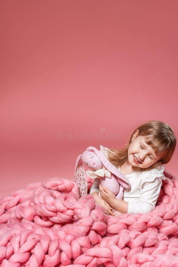 Glückliches Baby auf dem rosa korallenroten Hintergrund umfasst mit Decke und Merino lizenzfreies stockfoto
