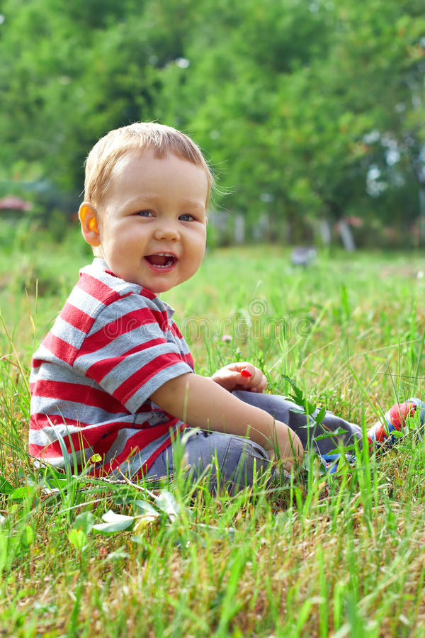 Glückliches Baby, das auf grünem Sommerfeld sitzt lizenzfreies stockbild