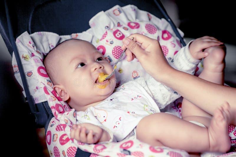 Glückliches Baby, das auf Prahlerstuhl sitzt stockfotos