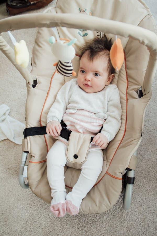 Glückliches Baby, das in einem Prahler-Stuhl sich entspannt stockfotografie