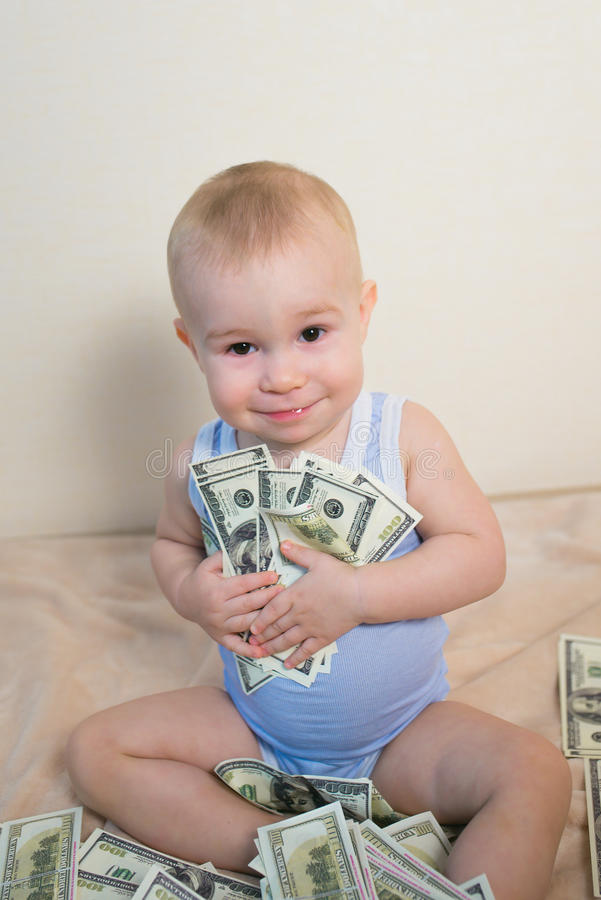 Glückliches Baby, das mit dem Geld, Hunderte von den Dollar umarmend spielt lizenzfreie stockfotografie