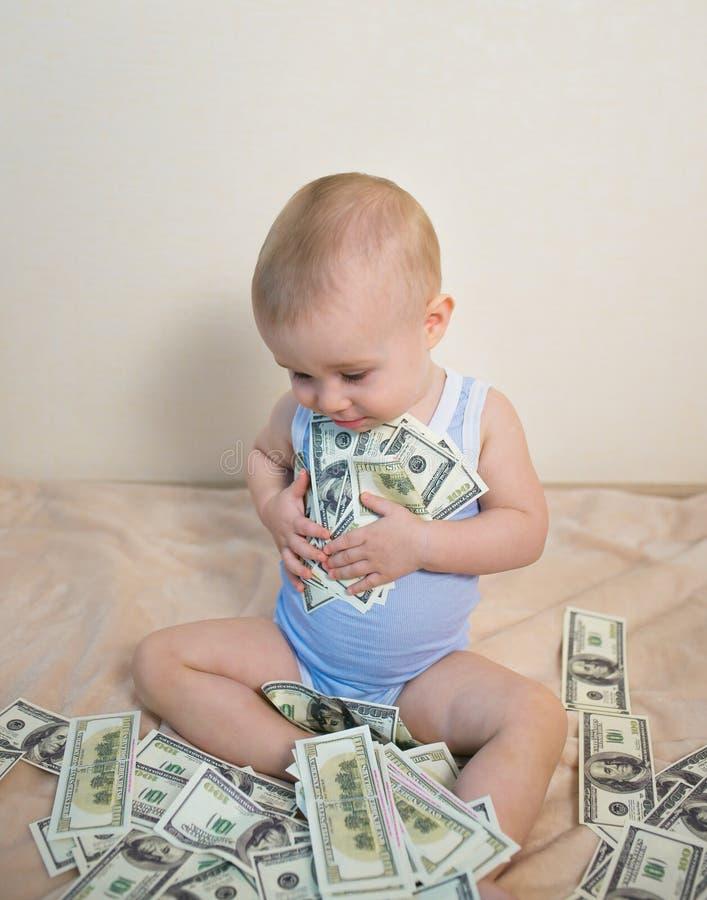 Glückliches Baby, das mit dem Geld, Hunderte von den Dollar umarmend spielt stockfoto