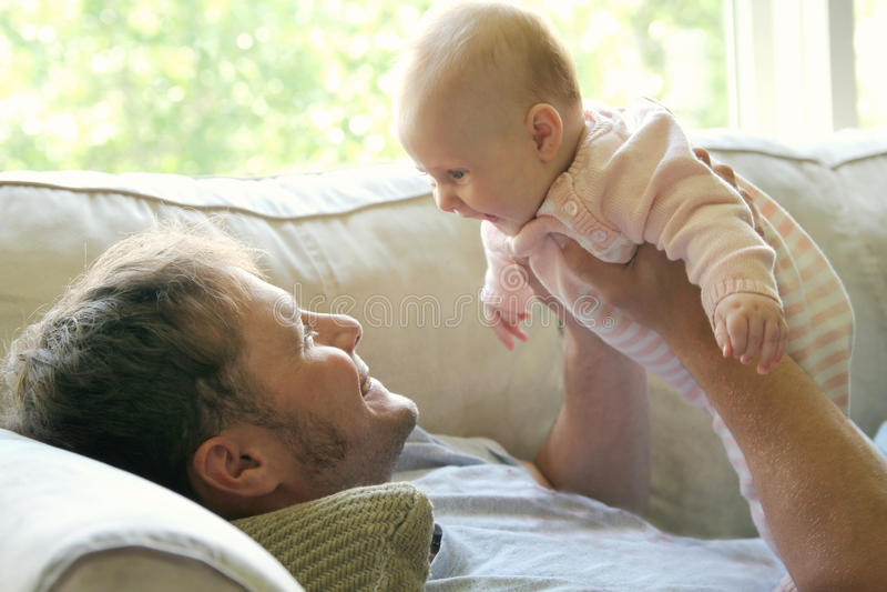 Glückliches Baby, das zu Hause mit Vater spielt stockbilder