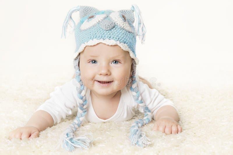 Glückliches Baby in der blauen Strickmütze, lächelnder Kinderjunge, der Kopf hebt lizenzfreie stockfotografie