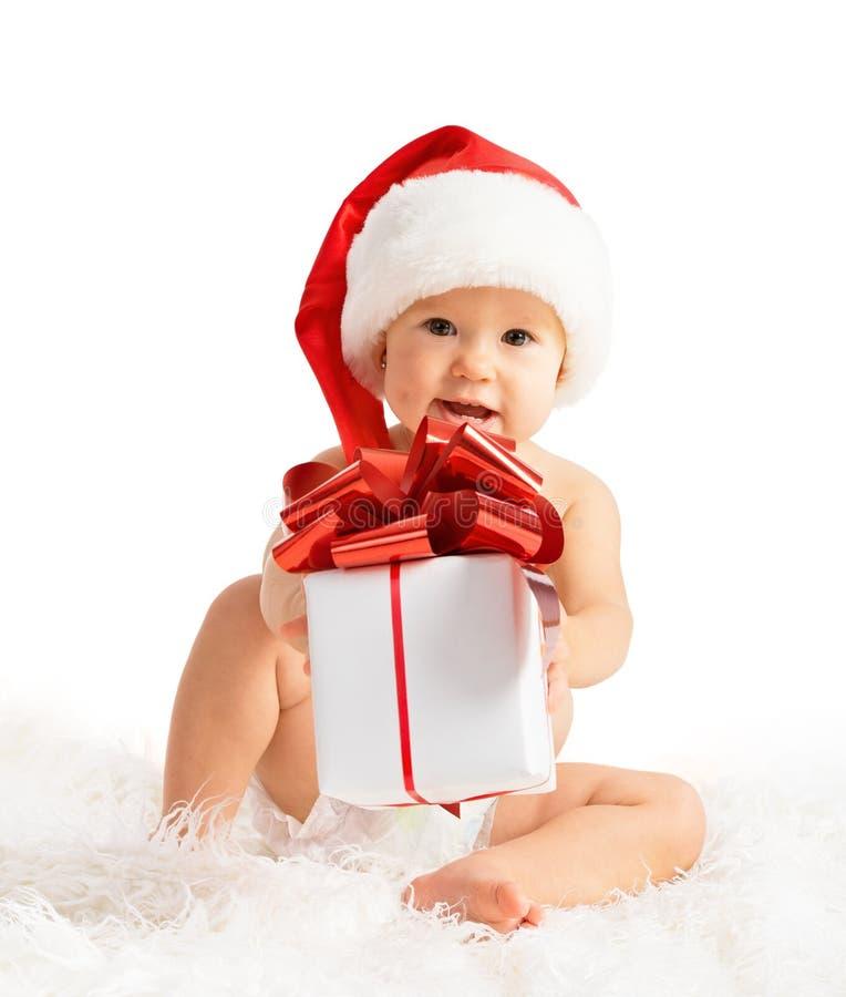 Glückliches Baby in einem Weihnachtshut mit einem Geschenk lokalisiert stockfotos