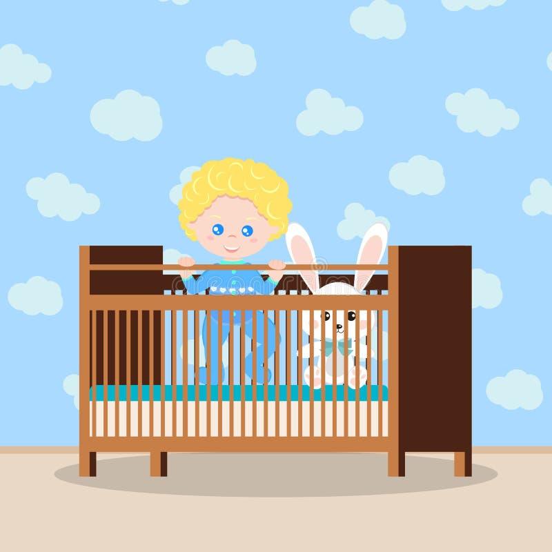 Glückliches Baby im blauen Sleepwear, der in der hölzernen Krippe mit weichem Spielzeug steht lizenzfreie abbildung