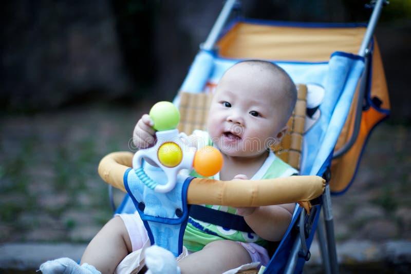 Glückliches Baby im Spaziergänger, der Spielzeug spielt stockbild