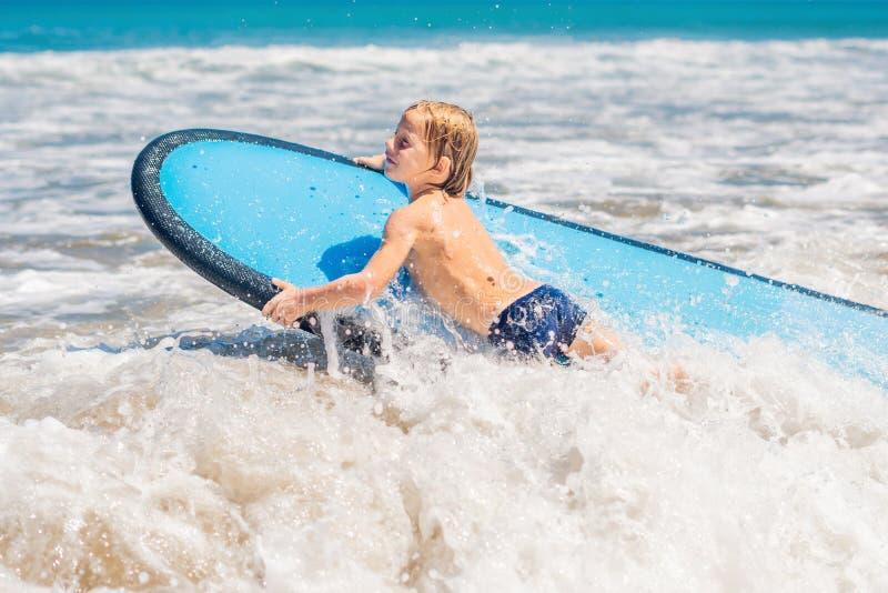 Glückliches Baby - junge Surferfahrt auf Surfbrett mit Spaß auf Meer lizenzfreie stockbilder