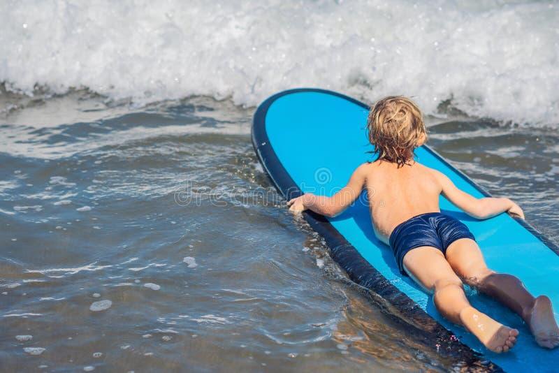 Glückliches Baby - junge Surferfahrt auf Surfbrett mit Spaß auf Meer stockbild