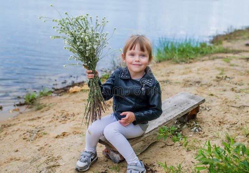 Glückliches Baby mit einem Blumenstrauß von Wildflowers nahe See stockfotografie