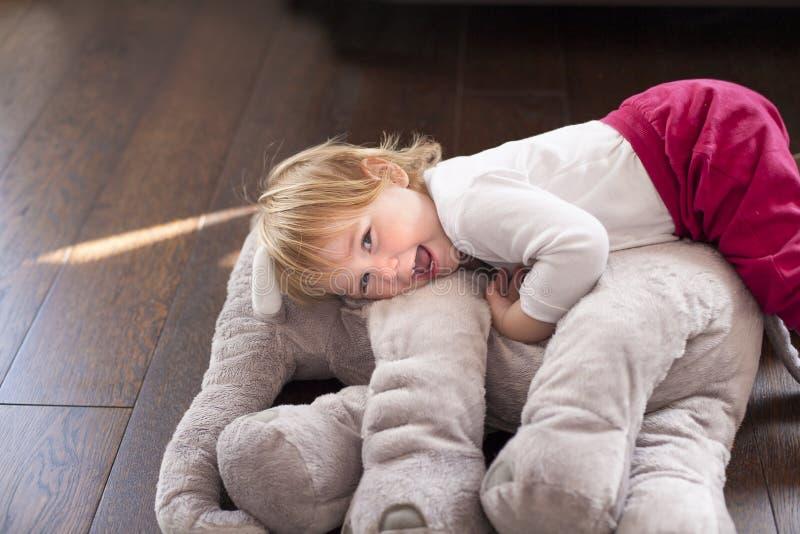 Glückliches Baby umfasste Elefantplüsch lizenzfreie stockbilder