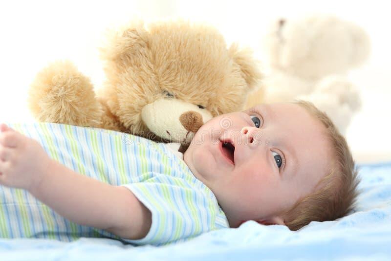 Glückliches Baby und Teddybär betreffen ein Bett lizenzfreies stockfoto