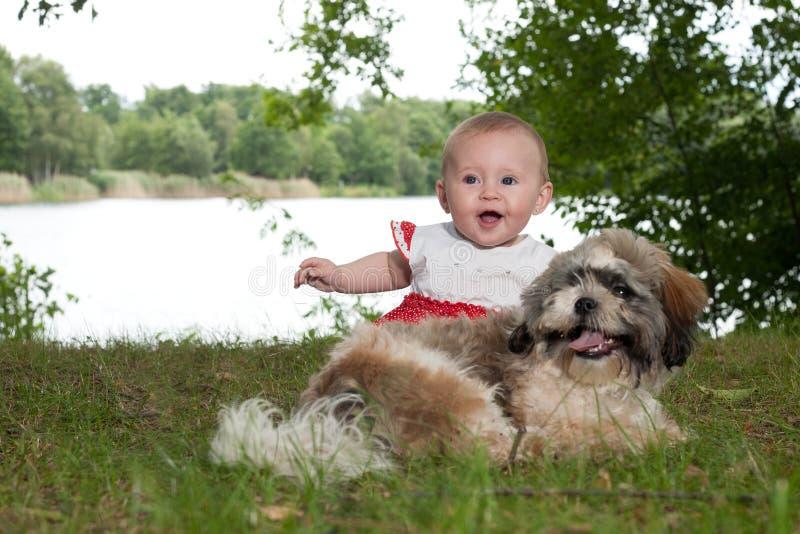 Glückliches Baby und Welpe nahe dem See lizenzfreie stockbilder