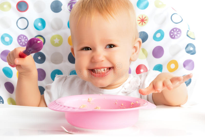 Glückliches Babykind isst sich mit einem Löffel lizenzfreie stockbilder