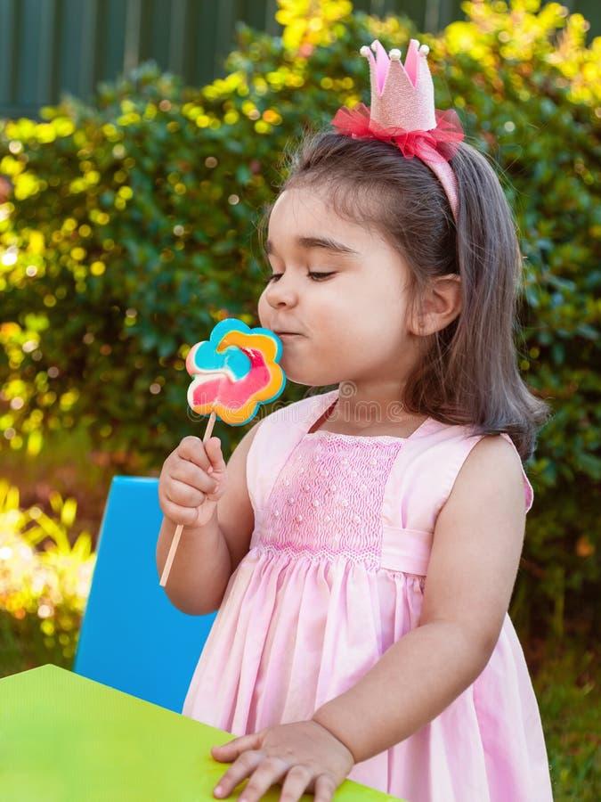 Glückliches Babykleinkindmädchen, das einen großen bunten Lutschergeruch, -geruch oder -aroma riecht und genießt stockfoto