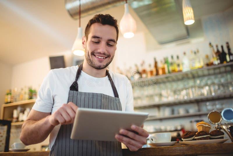 Glückliches barista unter Verwendung der digitalen Tablette am Café stockfoto