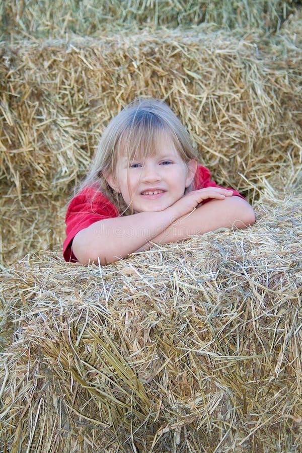 Glückliches Bauernhofmädchen im Stroh. lizenzfreies stockbild