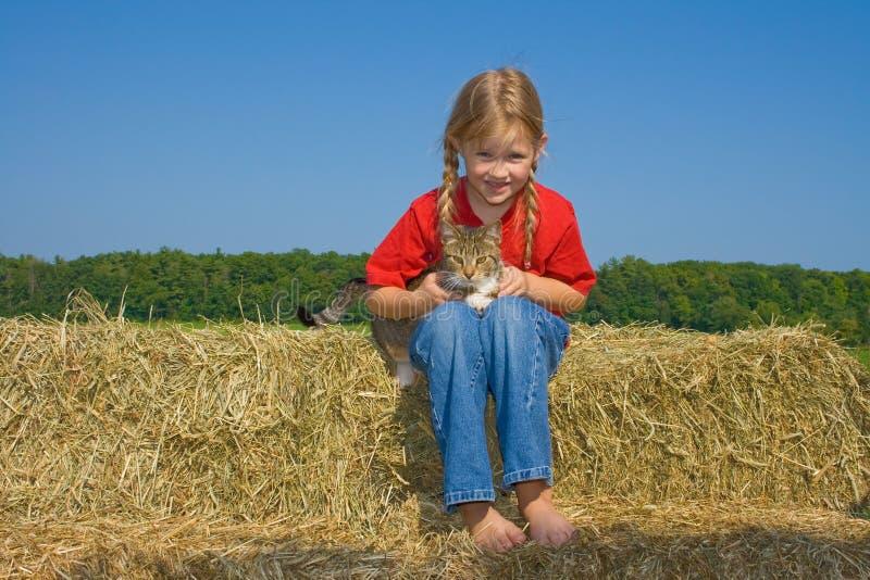 Glückliches Bauernhofmädchen mit ihrer Miezekatze. lizenzfreie stockfotos