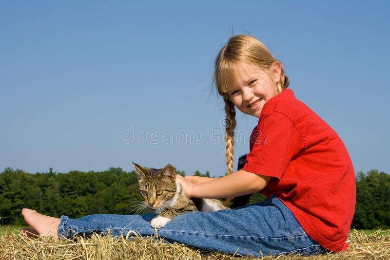 Glückliches Bauernhofmädchen mit Katze. stockfotos