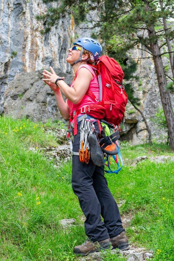 Glückliches Bergsteigermädchen mit einem roten Rucksack, quickdraws, kletternde Schuhe, weissen die Tasche, die zu ihrem Geschirr lizenzfreie stockfotografie