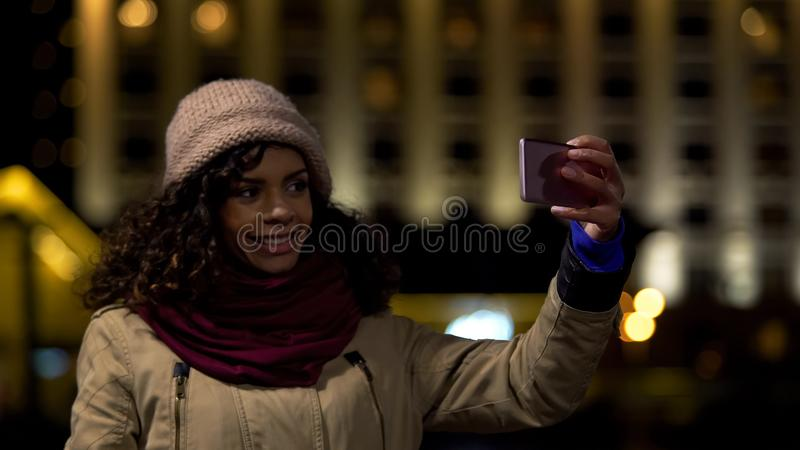 Glückliches biracial Mädchen, das selfie gegen Nachtstadthintergrund zu nimmt, Gedächtnisse zu sparen lizenzfreies stockfoto