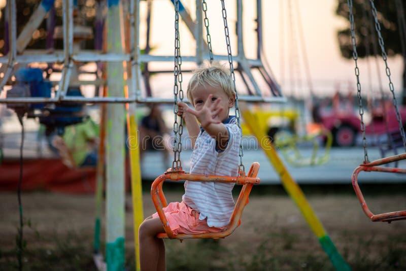 Glückliches blondes Kleinkindkind, das an der Kamera reitet ein Karussell wellenartig bewegt lizenzfreie stockbilder