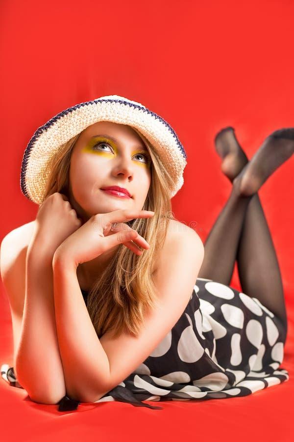 Glückliches blondes Lügen im Strandhut stockbilder