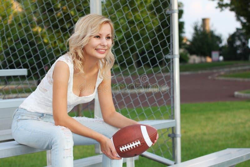 Glückliches blondes Mädchen mit amerikanischem Fußball. Lächelnde nette schöne junge Frau, die auf der Bank sitzt. Draußen. Fan de lizenzfreies stockfoto