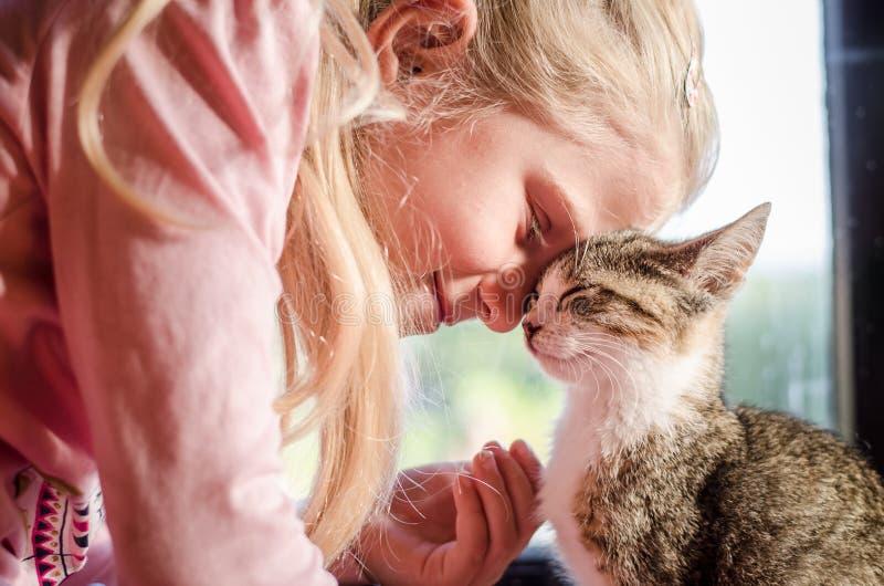 Glückliches blondes Mädchen mit Katze lizenzfreies stockfoto