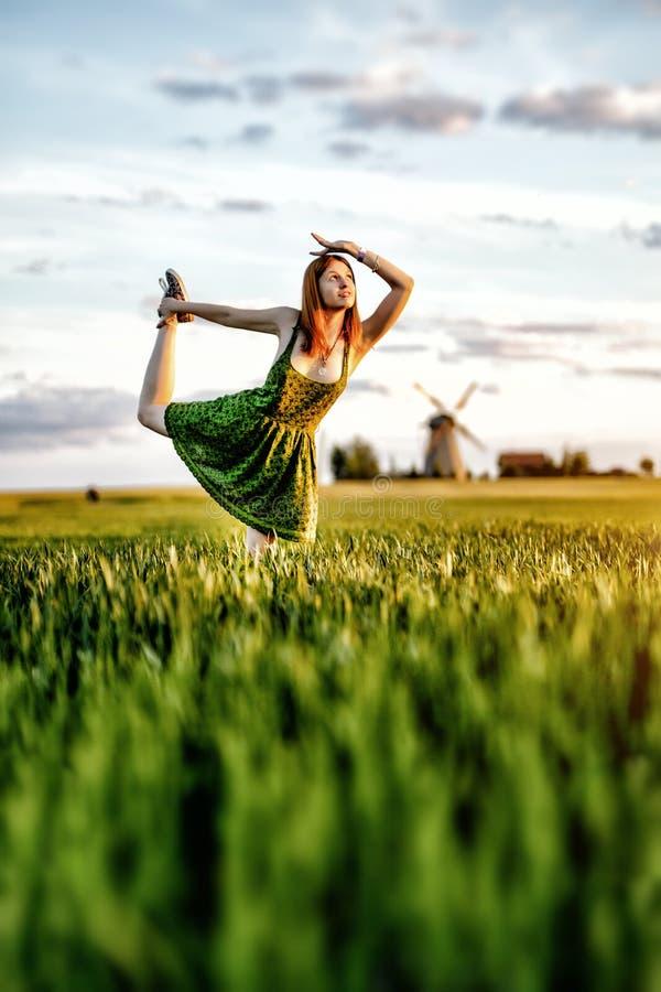 Glückliches blondes Mädchen, voll tanzend auf einem Gebiet von gelben Blumen Hintergrund der Sommerzeit und der blauen Himmel lizenzfreies stockfoto
