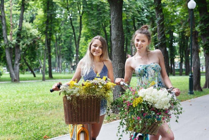 Glückliches boho schicke Mädchen fahren zusammen auf Fahrräder im Park stockfoto
