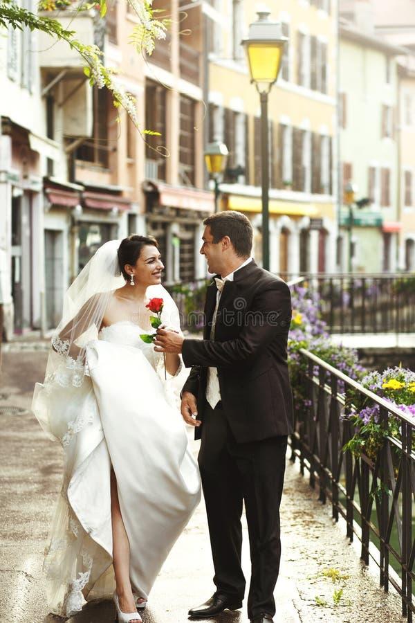 Glückliches Braut- und Bräutigamhändchenhalten des verheirateten Paars auf alte Franzosen lizenzfreies stockbild