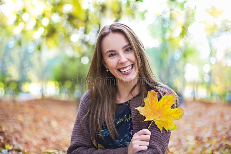 Glückliches brunette Mädchen, das im Herbstpark auf gelbem Baumhintergrund aufwirft lizenzfreie stockfotos