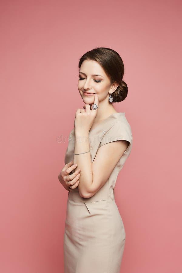 Glückliches brunette vorbildliches Mädchen mit einem schönen Lächeln in einem beige Kleid mit dem stilvollen Schmuck lokalisiert  stockfotografie