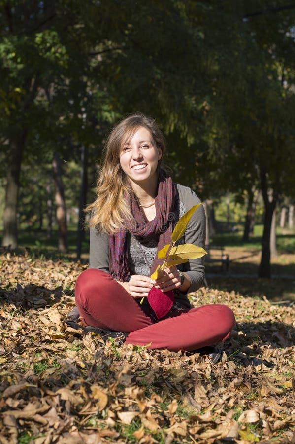 Glückliches Brunettemädchen, das unter gelbem Herbstlaub sitzt stockfotos