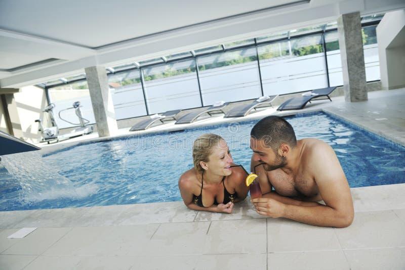 Glückliches cople, das am Swimmingpool sich entspannt stockbild