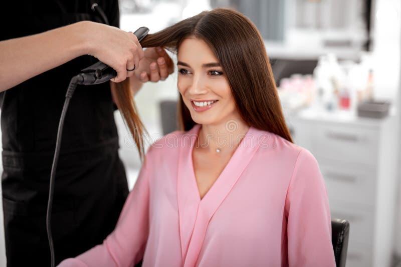 Glückliches Damenlächeln und -friseur ihr Haar gerade herstellend lizenzfreie stockbilder