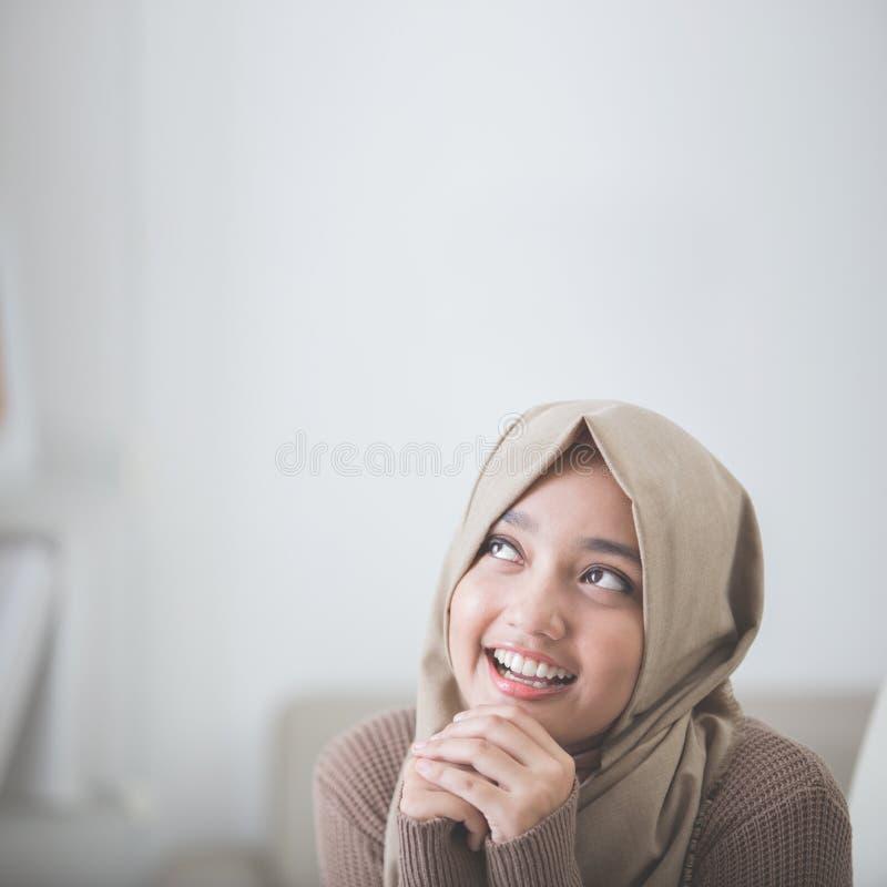 Glückliches Denken der jungen Frau stockfoto